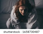 Small photo of overhead view of demoniacal smiling woman in nightgown sitting in bed