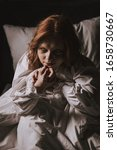 Small photo of Paranormal demoniacal girl in nightgown sitting in bed