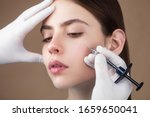 Small photo of Anti-aging face treatment. Close up side on portrait of young pretty woman relaxing on rejuvenation procedure of cheek bone zone by specialist