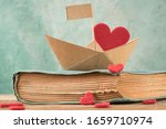 Paper Boat On An Old Book On...