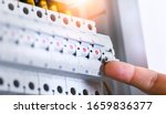 Small photo of Male hand switching on the electric switch box with automatic fuses. Electrician installing electric cable wires and fuse switch boxes. Multimeter in hands of electricians.
