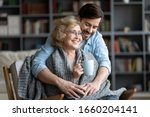 Small photo of Loving young man take care of happy middle-aged mother sit in chair drinking tea enjoying family weekend in living room, thankful grown-up adult son hug show gratitude and affection to mature mom