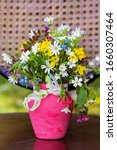 Small photo of Beautiful Wild Spring Flowers and Daisies in a Small Pink Vase