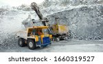 Work of mining machines in a snow-covered limestone quarry, dump truck and excavator in a stone ore loading, panorama. Mining industry.