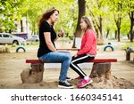 Small photo of Mom and daughter sitting on a bench and talking, woman trying to impart to teenage daughter a woman's wisdom, intuition. The daughter smiles and doesn't understand what mom wants to tell her