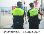 """Small photo of Spanish police squad formation back view with """"Local Police"""" logo emblem on uniform maintain public order in the streets of Alicante, Spain"""