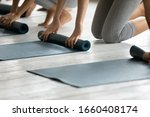 Small photo of Sporty women barefoot kneeling on warm floor fold up personal mats finished yoga session at studio close up. Training class like-minded females, healthy body and mind, lifestyle and wellness concept