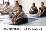 Small photo of Yoga session led by Indian ethnicity young female coach, group of multi-ethnic like-minded people sitting in mats performing Seated Forward Bend, asana calms brain helps relieve stress, stretches body
