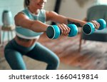 Blurred and cropped image of a beautiful young athletic girl in leggings and top crouches with dumbbells at home. Sport, healthy lifestyle. - stock photo