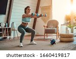 Small photo of Beautiful young athletic girl in leggings and top crouches with dumbbells at home. Sport, healthy lifestyle.