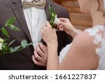 Close up of bride putting on boutonniere to the groom