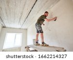 Apartment remodel. Worker is standing on wooden stand and puttying the walls indoors at small room. A guy with a beard in a t-shirt and jeans is smeared paint - stock photo