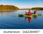 Two Men On Kayaks Fish In...