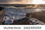 Small photo of Gusty winds on the beach whipping up foam