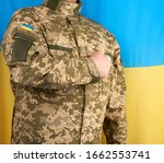 Ukrainian man a warrior dressed in a military pixel uniform stands against the background of the national flag of Ukraine, soldier put his right hand to his chest as a sign of respect, honor