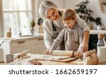 Small photo of happy family grandmother and grandson child cook in the kitchen, knead dough and bake cookies