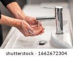 Washing hands man rinsing soap...