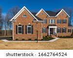 Small photo of Newly constructed mansion style estate home with curb appeal landscaping, brick facade, triple peak gable, symmetric arched windows with shutter, portico covered w/ metal hip roof, Quoin brick corner