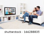young couple sitting on couch... | Shutterstock . vector #166288835