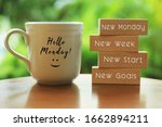 Small photo of Hello Monday concept with inspirational quote on wooden blocks - New Monday. New Week, New Start. New Goals. And a smiling face on a white morning cup of coffee or tea.