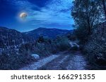 Empty ground mountain road with  near the  forest with cloudy sky in midnight light - stock photo