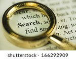 Macro Image Of A Magnifying Glass Over The Search Word In A Dictionary - stock photo