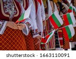 Small photo of Bulgarian Flag. Woman holding Flag of Bulgaria in traditional clothing. Day of Liberation parade. National holiday with people celebrating. Patriotic scene people waving flags.