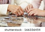Small photo of Old hands solving jigsaw puzzle in a nursing home