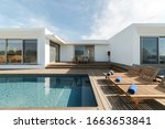 Small photo of Wooden lounge chairs in modern villa pool and deck