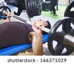 man doing bench press in gym. | Shutterstock . vector #166371029