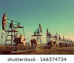 many working oil pumps in row under blue sky - vintage retro style - stock photo
