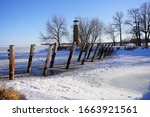 Old vintage historical Asylum Point Lighthouse standing off of the frozen Lake Winnebago out in Oshkosh, Wisconsin during the cold Winter season.
