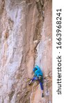 Small photo of A woman in a helmet climbs a beautiful orange rock. Climbing protective equipment. Safety in climbing. Rock climber overcomes a difficult route on a natural terrain. Rock climbing in Turkey.