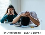 Small photo of stressed young couple upset and worried about credit card and family budget expense cost bills and calculator on desk in home, plan money cost saving, investment, business finance and expenses concept