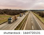 Small photo of Loaded timber trucks transport timber logs with an overload on the highway. Wood Cargo Transporter. The concept of transportation of timber and wood