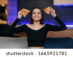 Small photo of Excited happy young woman in kitchen plaing with pizza slices. Cover eyes with food. Carefree housekeeper very playful. Wear white dressing gown. Careless houseswife.