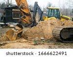 Excavators machine in construction site on sky background.