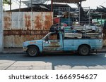 Chon Buri, Thailand - February 22, 2020: The old blue pickup car is packing junk, which is junk from the household, for sale. - stock photo