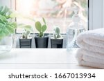 Small photo of Stack of Clean towels with bottle of alcohol rub gel and houseplant on white wooden table in kitchenroom. Copy space.