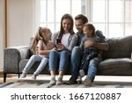 Small photo of Full length joyful family of four sitting on couch, watching funny video together at home. Smiling young woman taking selfie photo with affectionate husband and cute kids son daughter on smartphone.