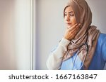 Shot of a young muslim female doctor looking stressed out while standing at a window in a hospital. Upset female nurse standing in hospital corridor. Medical professional looking unhappy. - stock photo