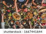 Flat-lay of family feasting with Turkish cuisine lamb chops, quince, bean, vegetable salad, babaganush, rice pilav, pumpkin dessert, lemonade over rustic table, top view. Middle East cuisine