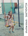 Small photo of Swing ride - swinging girl. Teenager riding a swing. A girl of 9 years old rides a swing in the yard in the summer. A child on a swing.Girl in a striped dress.Teenager on a walk.Girl 8 or 9 years old.