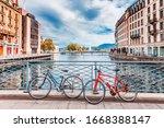 Switzerland, Geneva city. Classical view of Swiss famous city Geneva - capital buildings at lake Geneva banks and bicycles at pedestrian  bridge.