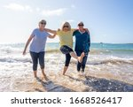 Lovely group of senior girl friends on their 60s walking and having fun splashing water on sea. Three mature healthy retired females Laughing and enjoying retirement and outdoors active lifestyle. - stock photo