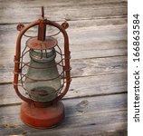 old kerosene  lamp on a wooden... | Shutterstock . vector #166863584