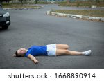 Small photo of Downed girl by car, young unconscious woman lying on road, asphault, suffering from pain, injury or trauma. Inattentive person, female was hit by careless driver. Accident on road. Dangerous situation