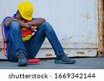 American African engineer or technician worker man sit close to cargo container and he look tire and also sleepy or lost job. Concept of good system and manager support for better industrial business. - stock photo