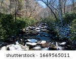 A rocky creek flowing through a snow covered forest at Alum Cave Trail in the Great Smoky Mountains