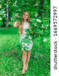 Small photo of Spring portrait of a charming blond woman wearing beautiful white dress standing next to blooming rowan tree with white flowers.